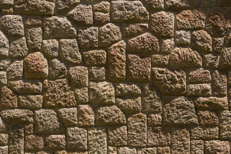 Dry stone wall texture background, in searing light.