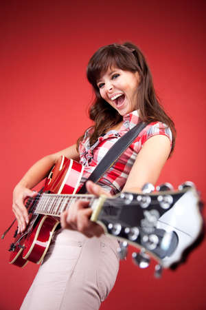 young woman playing a bass guitar in front of a red wall 6954 photo