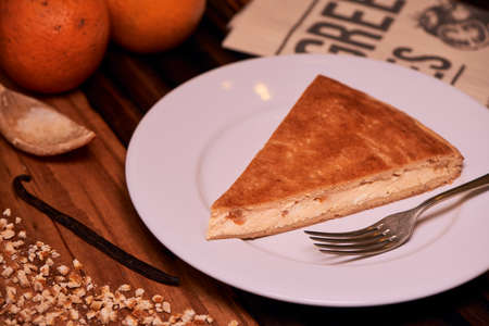 Portion of Homemade Italian Ricotta Cheesecake with chopped candied orange peels on wooden background.
