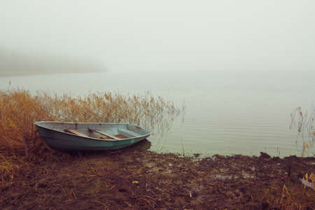Fishing boat on the lake in the fog