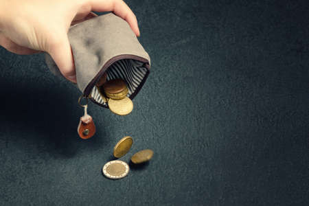 Several coins fall on the table from an empty wallet in a womans hand, poverty, crisis, bankruptcy and financial problems concept