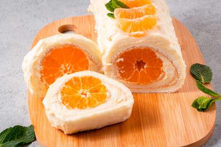 Rollo de bizcocho dulce relleno de nata montada y mandarina