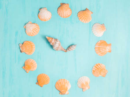 Blue sea background with clocks from seashells, summer holiday and vacation time concept