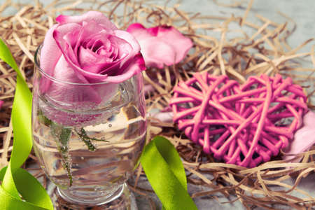 Pink rose in a glass with water and decorations on the table