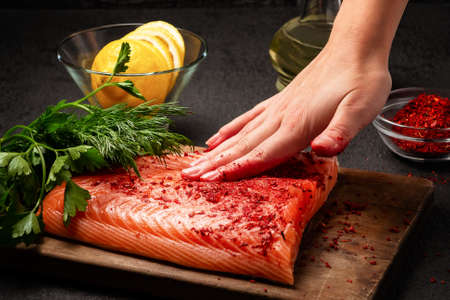 Une main féminine enduit un morceau de filet de saumon allongé sur une planche à découper en bois avec des épices - photo, image Banque d'images