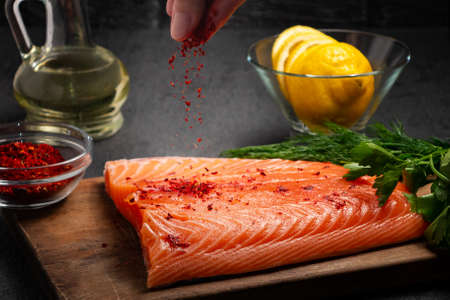 Female hand sprinkles a piece of salmon fillet lying on a wooden cutting board with spices - photo, image Stock Photo