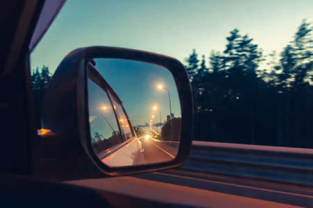 Night highway in the side mirror while driving - photo, image. Soft focus Фото со стока