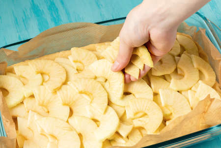 Putting apples on the dough in a baking dish. Cooking Apple Pie - photo, image