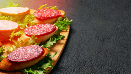 Several sandwiches with sausage and salami and sauce on a black board, background with copyspace