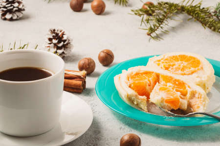 Sweet roll with whipped cream and tangerine filling and Christmas decorations and a cup of coffee Stock Photo