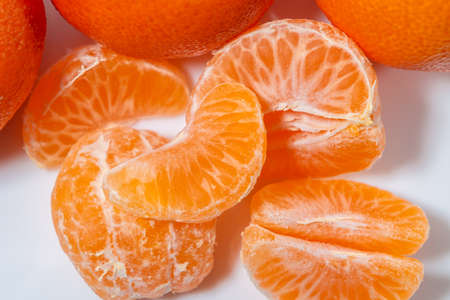 Several whole and peeled ripe tangerines on a white plate
