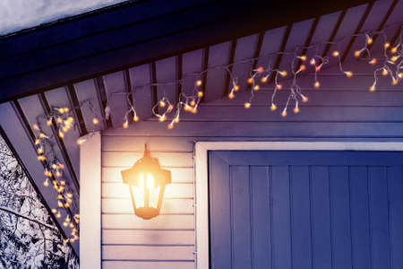 Porch of the house is decorated in the traditional Scandinavian style with a lantern and Christmas lights - concept of home warmth, comfort, family holiday
