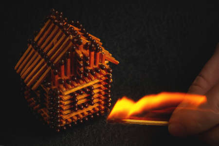 hand with a burning match sets fire to the house model of matches, risk, property Insurance protection or ignition of combustible materials concept