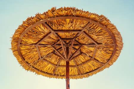 Beach umbrella made of straw against the blue sky