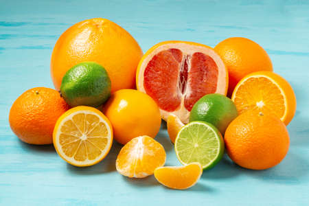 group of whole and sliced citrus fruits - tangerines, lemons, limes, oranges, grapefruits on the surface of the blue table - image