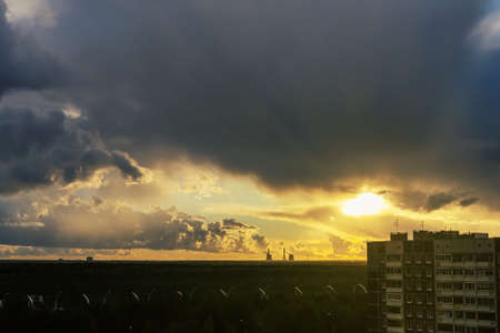 Suns rays breaking through the thunderclouds on the outskirts of the city
