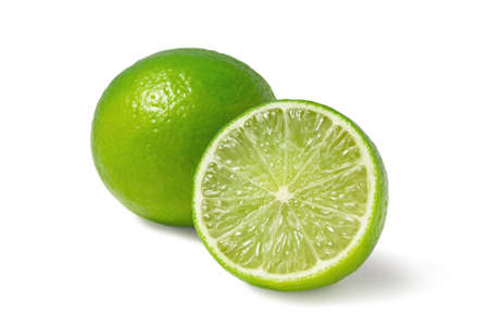 Fresh ripe limes, one whole and one half isolated on white background with shadow - image