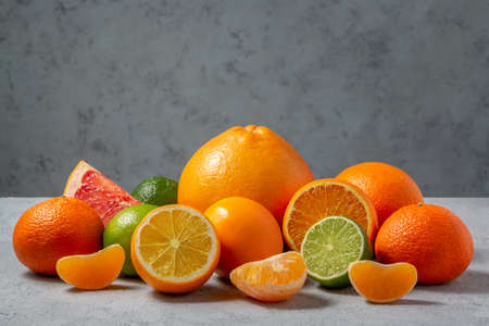 group of citrus fruits - tangerines, lemons, limes, oranges, grapefruits on the surface of a gray table against a gray wall - image with copy space