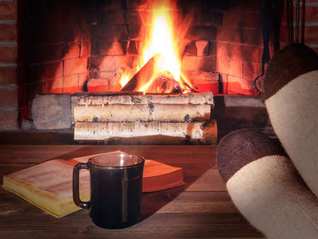 Cup of tea, book, womens feet in warm socks on a wooden table opposite a burning fireplace