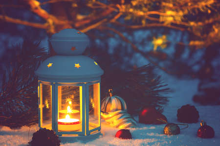 Lantern with a burning candle and Christmas decorations on a snow-covered table
