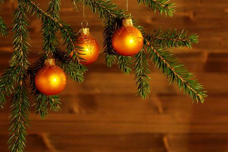 Adornos navideños de color naranja sobre ramas de abeto en el fondo de una pared de madera. Fondo de Navidad o año nuevo