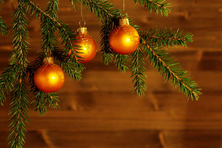Orange Christmas ornaments on spruce branches on the background of a wooden wall. New Year or Christmas background
