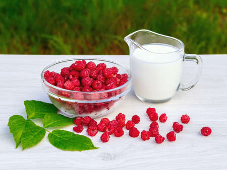 Fresh raspberries in a glass bowl and natural iogurt on a white wooden table. Healthy eating concept 免版税图像