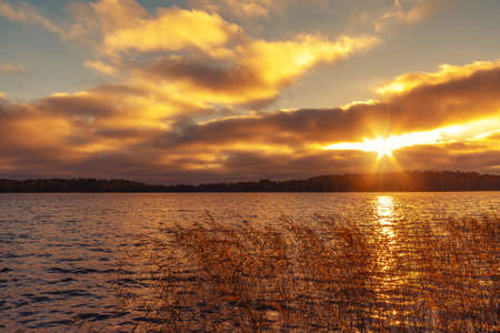 Suns rays make their way through the clouds above the lake at sunset. Beautiful evening landscape background 写真素材