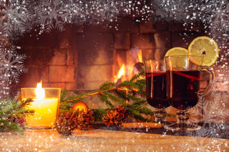 Two glasses with mulled wine, a candle, fir branches with decorations on a wooden table against the background of a burning fireplace framed by hoarfrost and snowflakes. Romantic christmas concept