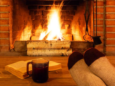 Cup of tea, book, womens feet in warm socks on a wooden table opposite a burning fireplace Reklamní fotografie
