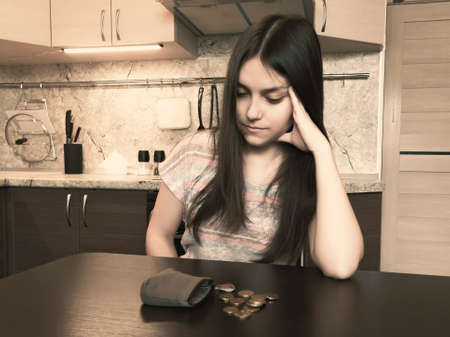 Concept of financial problems, a young disappointed woman with long dark hair, sits next to an old empty wallet with several coins on the table