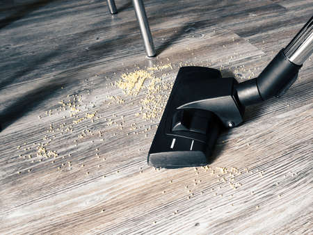 Garbage on the floor is cleaned with a vacuum cleaner. In the frame, a brush from a vacuum cleaner, legs of tables and chairs, a floor with a pattern for wood