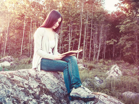 Young pretty girl reading a book sitting on a large rock in the forest