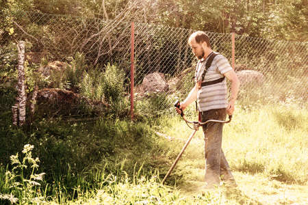 A man mows the grass in his garden with a trimmer Stock Photo