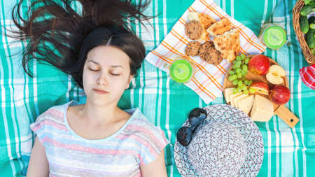 Young girl with long dark hair is lying on a plaid on a picnic on a summer day - summer holidays and vacation concept