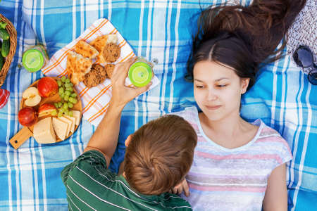 Young loving couple resting on a picnic on a summer day Reklamní fotografie