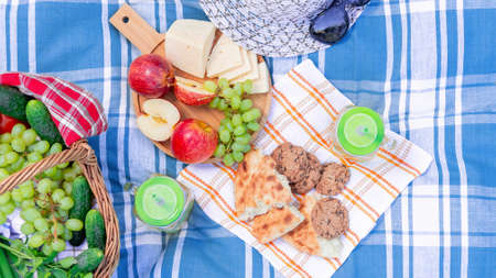 Picnic on the grass on a summer day - basket, grapes, cheese, bread, apples - a concept of summer outdoor recreation