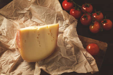 Piece of hard cheese on craft paper and cherry tomatoes on a wooden table