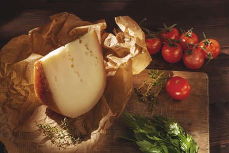 Piece of hard cheese on kraft paper, parsley, thyme, and cherry tomatoes on a wooden table