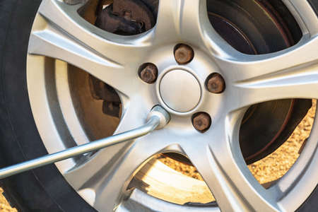 Replacing the wheels on the highway, unscrewing the nuts with a wrench
