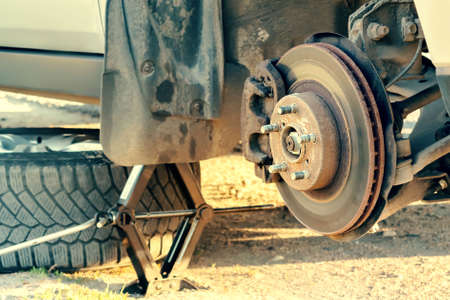 Replacement wheels on the highway, the car is jacked, the wheel is removed, there is a spare wheel Reklamní fotografie