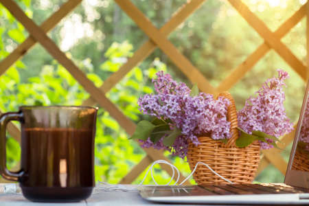 Laptop, cup of coffee, cookies and a basket of lilac flowers on a white wooden table in the summer terrace - concept of remote work, online business, self-employment