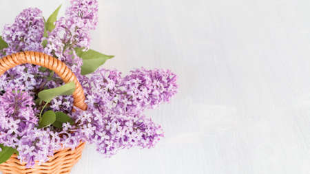 Basket with a bouquet of lilac flowers on a white wooden table, banner with place for text Imagens