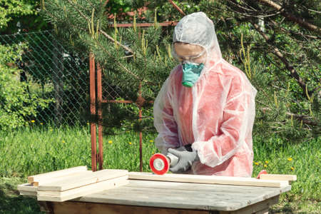 Woman carpenter in respirator, goggles and overalls handles a wooden board with a Angle grinder