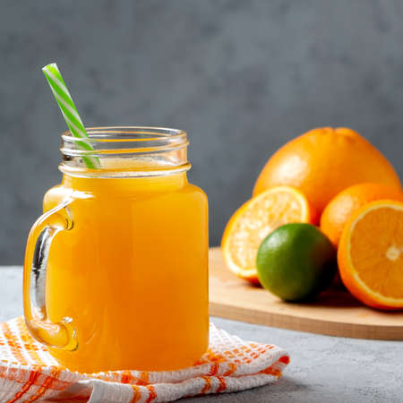 Freshly made citrus juice from oranges, grapefruit and lime in a jar-mug with a straw on gray table