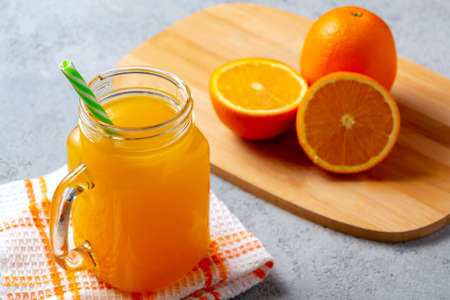 Freshly made citrus juice from oranges in a jar-mug with a straw on gray table Stock Photo