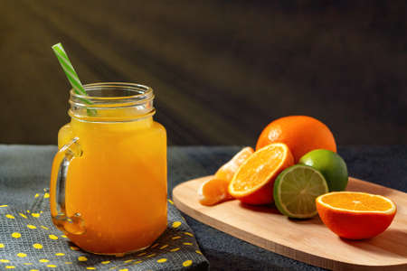 Freshly made citrus juice from oranges, grapefruit and lime in a jar-mug with a straw on black table