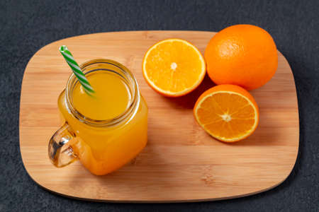 Freshly prepared citrus juice from oranges in a jar-mug with a straw on a cutting board