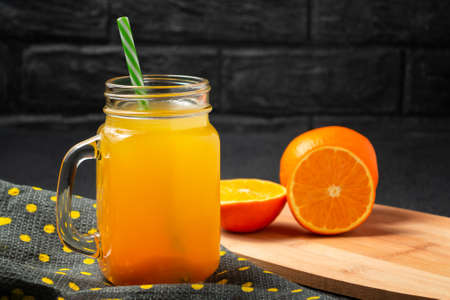 Freshly made citrus juice from oranges in a jar-mug with a straw on grey table Stock Photo