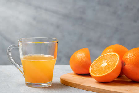woman squeezes orange juice in a glass cup